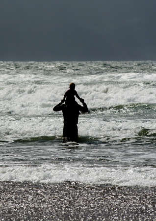 the entering: Man with Child on his Shoulders Entering Water Stock Photo