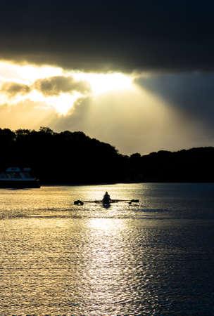 synchronous: Rowing Boat on Sunset Lake Stock Photo