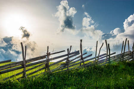 Old wooden fence in front of cloudy sky Stock Photo