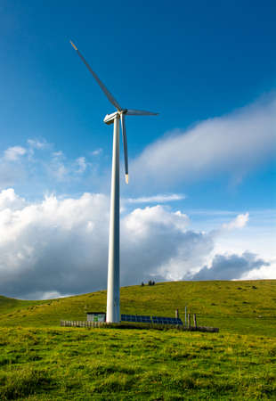 Wind turbine on hill in front of cloudy sky