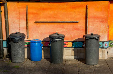 Dustbins in Front of Orange Wall