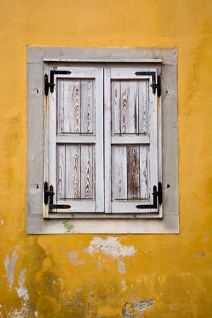 White Wooden Windows on Yellow Stone Wall Stock Photo