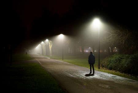 Pojedyncza osoba spacerująca po ulicy w ciemną noc