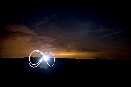 Infinity Symbol with Flashlight unter Nightsky with Stars