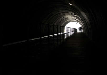 Silhouette Of A Couple In Front Of Bright Light At The End Of A Dark Tunnel