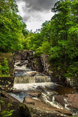 Scenic Waterfall In Forest Landscape In Scotland