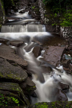 Scenic Long Exposed Waterfall In Forest Landscape In Scotland Reklamní fotografie