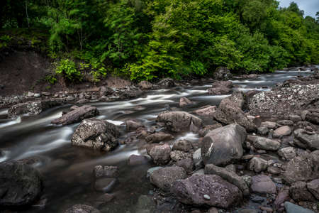 Wild Mountain River Streaming Through Green Forest in Scotland Reklamní fotografie