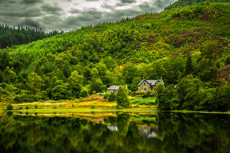 Lonesome House At Calm And Smooth Lake In Scotland Reklamní fotografie