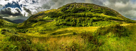 Green Valley And High Mountain With Ancient Railway Bridge In Scotland