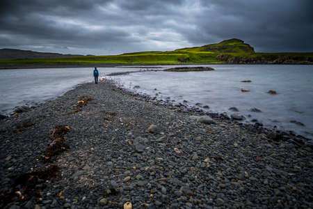 Lonely Person On Stony Sandbank At Low Tide On The Isle Of Skye In Scotland