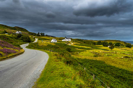 Abandoned Single Track Road Through Scenic Hills With Houses At The Coast Of The Isle Of Skye In Scotland