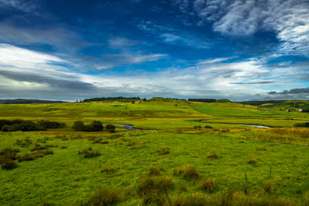 Scenic Landscape With Small River And Pastures With Flocks Of Sheep On The Isle Of Skye In Scotland