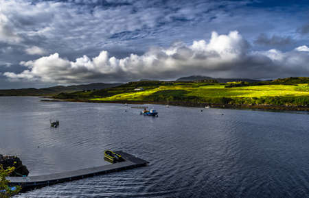 Picturesque Settlement And Small Boats In Harbor Of Dunvegan At The Coast Of The Isle Of Skye In Scotland