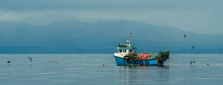 Small Fishing Boat With Lobster Pods And Seagulls On Calm Atlantic In The Front Of The Hebride Islands Stock Photo