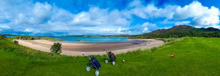 Campo da golf con carrelli e mazze sulla spiaggia di sabbia bianca di Gairloch in Scozia Archivio Fotografico