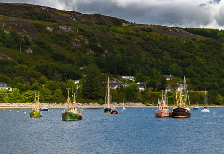 Old Weathered Fishing Boats Anchored In The Harbor Of Ullapool At Loch Broom In Scotland 免版税图像