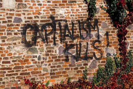 Capitalism Kills Graffiti On Brick Wall With Ivy