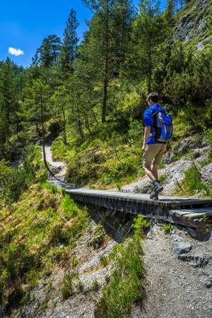 Young Man Walks Over Wooden Bridge On Hiking Trail In Ötschergräben In Austria 스톡 콘텐츠