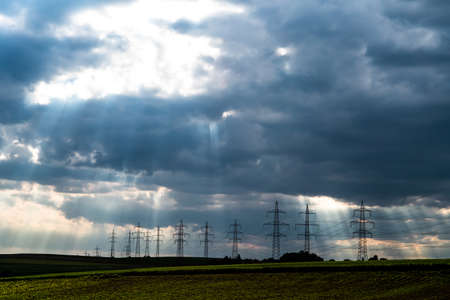 Pylons With High Voltage Energy Wires In Farmland At Stormy Weather Foto de archivo