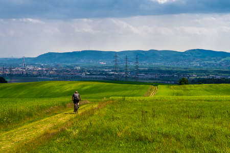 Man Rides Mountainbike In Rural Landscape In Front Of Skyline Of Vienna In Austria Foto de archivo