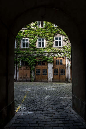 Courtyard Of A HIstoric Building With Wooden Doors And Ivy Overgrown Walls