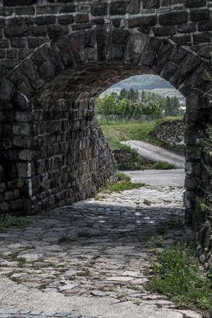 Old Stone Portal With Cobblestone Road To Rural Landscape