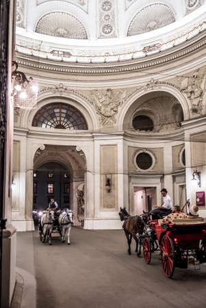 VIENNA, AUSTRIA - AUGUST 12, 2020: Fiaker Horses Pull Carriage With Tourists And Tour Guide Through Imperial Residence Passage Hofburg In Vienna In Austria