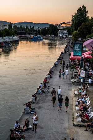 VIENNA, AUSTRIA - AUGUST 12, 2020:  People strolling and sitting at the river bank of the danube channel in the city of Vienna in Austria