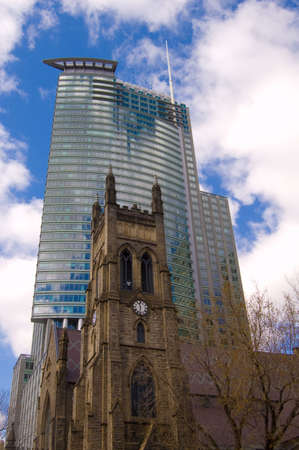 An old church in front of a modern skyscraper in downtown montreal
