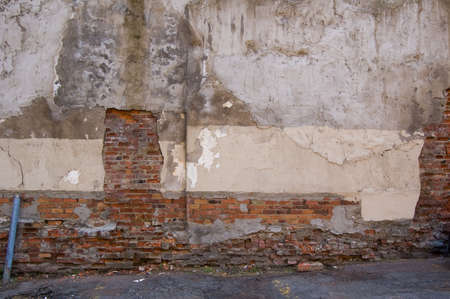 damaged: damaged wall with bricks showing through plaster surface