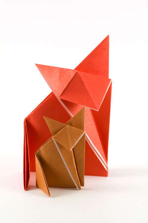 Two origami fox, made of orange and brown folded paper Stock Photo