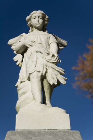 an old white stone cherub statue in a cemetary Stock Photo