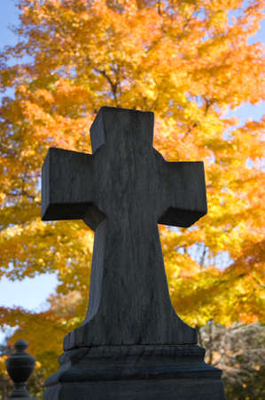 a close up of a cross on a cemetary monument at autumn