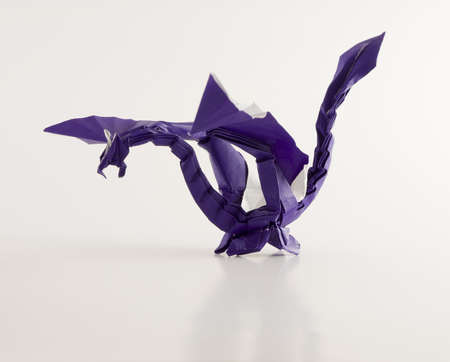a dragon made of folded purple paper isolated on white Stock Photo