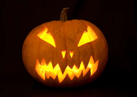 halloween decoration, a carved pumpkin illuminated with many candles