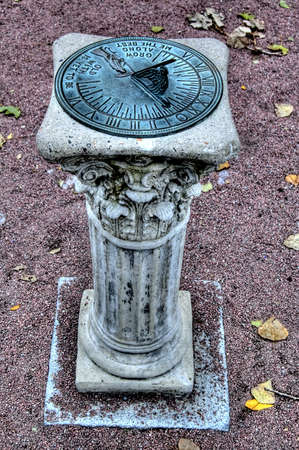 am old solar clock made of metal on a stone support