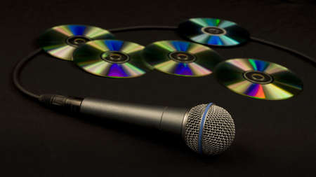 a microphone with many compact discs on the background