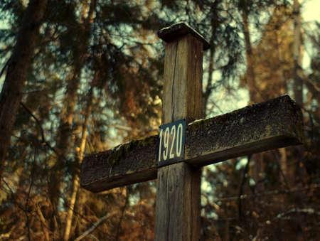 Vieja cruz con fecha od guerra polaco-sovi�tica en la oscuridad del bosque