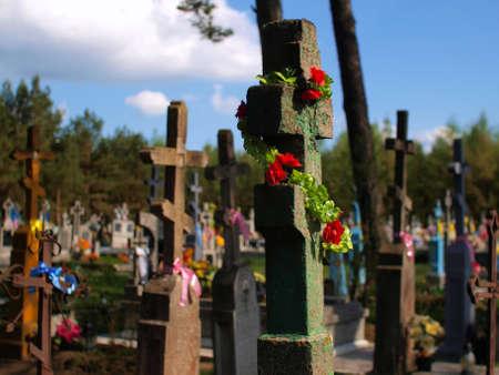 Fragmento del antiguo cementerio, con la cruz y las flores en primer plano Foto de archivo