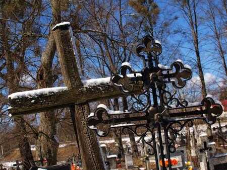 Dos cruces viejos cat�licos y ortodoxos en cementerio en invierno Foto de archivo