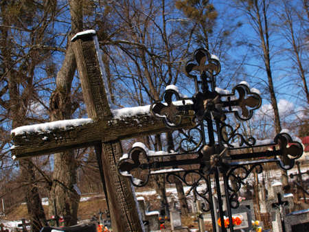 Two old crosses  catholic and orthodox  on cementary at winter time  photo