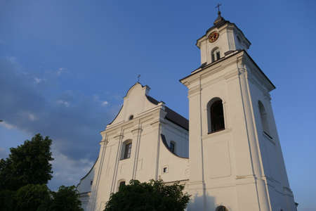 Church with belfry, a place of prayer confessing Christian religions against the blue sky on a sunny summer day in the small Polish town of Drohiczyn.