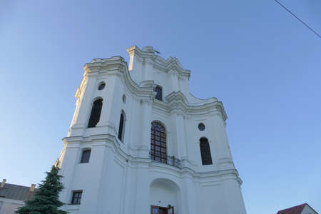Church with belfry, a place of prayer confessing Christian religions against the blue sky on a sunny summer day in the small town of Drohiczyn. Stock Photo