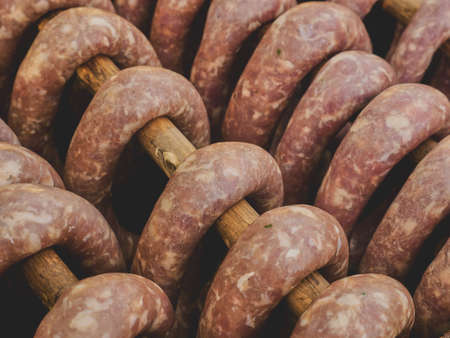 A group of smoked sausages hung on a stick over a smoke. This is a natural tasty product without preservatives or chemicals.