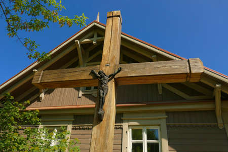 A wooden cross with a statue of Jesus on top of an old country house. A view that symbolizes human faith and hope. At the same time showing the relationship of the village with a broadly understood faith.