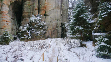 Rocks in the famous rocky city of Adrspach-Teplice rocks. Winter time trees, road, tourist routes and rocks covered with snow. known and popular place among tourists in the Czech Republic. Stock Photo