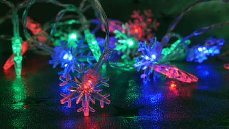 Colorful lights on an electronic Christmas tree chain in many colors on a green background. The climate of the upcoming Christmas.