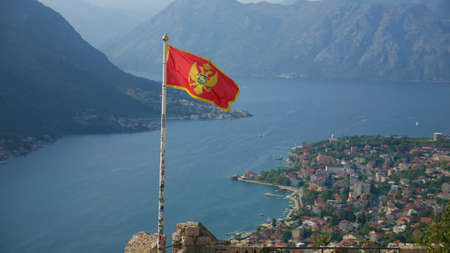 Montenegrin flag over Boka Kotorska. Picturesque bay and the historic city of Kotor inscribed on the  list
