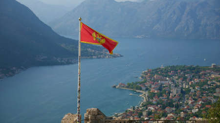 Montenegrin flag over Boka Kotorska. Picturesque bay and the historic city of Kotor inscribed on the UNESCO list